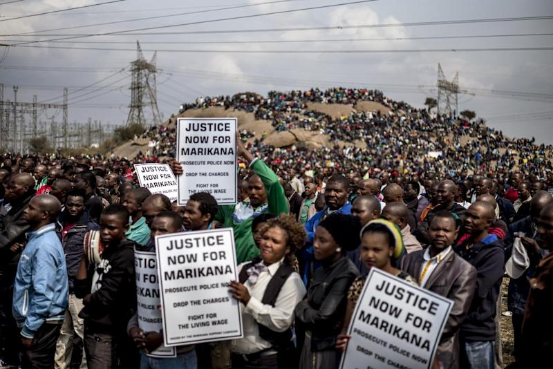 """People hold placards reading """"Justice now for Marikana, Prosecute police now, Drop the charges, Fight for the living wage"""" on August 16, 2014 in Marikana"""
