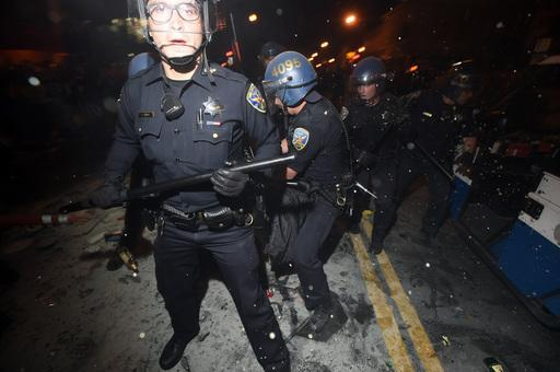 San Francisco police officers work to break up a large crowd who were celebrating after the San Francisco Giants won the World Series baseball game against the Kansas City Royals on Wednesday, Oct. 29, 2014, in San Francisco. There were several reports of fires being set and violence breaking out after the Giants win. (AP Photo/Noah Berger)