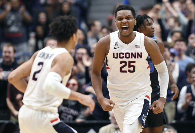 Connecticut's Josh Carlton (25) reacts toward teammate James Bouknight (2) after making a basket during the first half of the team's NCAA college basketball game against Memphis, Sunday, Feb. 16, 2020, in Hartford, Conn. (AP Photo/Jessica Hill)
