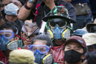 Pro-democracy protesters wear masks usually used to avoid tear gas during a protest in Bangkok, Thailand, Sunday, Sept. 20, 2020. The mass student-led rally that began Saturday is the largest in a series of protests this year, with thousands camping overnight near the royal palace, demanding for new elections and reform of the monarchy. (AP Photo/Wason Wanichakorn)