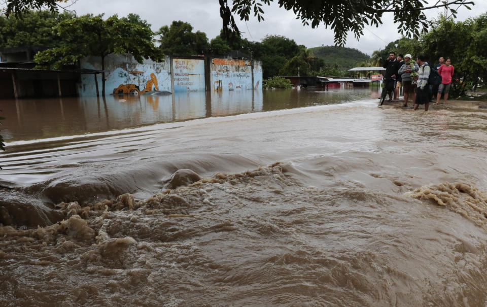 People stand on the edges of a flooded street after the passing of Iota in La Lima, Honduras, Wednesday, Nov. 18, 2020. Iota flooded stretches of Honduras still underwater from Hurricane Eta, after it hit Nicaragua Monday evening as a Category 4 hurricane and weakened as it moved across Central America, dissipating over El Salvador early Wednesday. (AP Photo/Delmer Martinez)