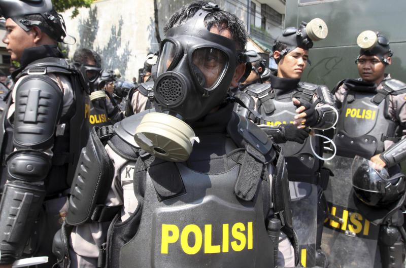 Indonesian riot policemen gather near Kerobokan prison in Denpasar, Indonesia, Thursday, Feb. 23, 2012. Indonesia started moving foreigners and a handful of other inmates from the overcrowded prison on Bali island Thursday after two days of rioting, officials said, as troops backed by water canons and armored vehicles surrounded the tense facility. (AP Photo/Firdia Lisnawati)