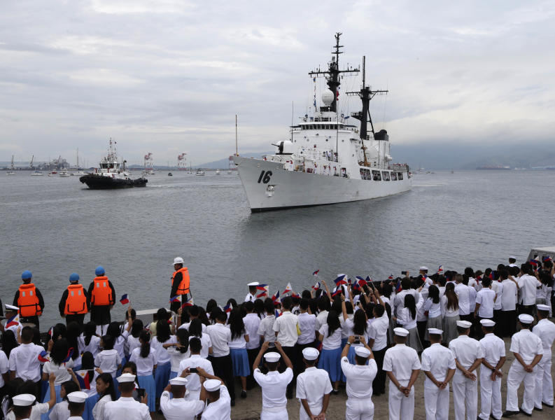 Students and other guests wave Philippine flags to welcome the second warship of the Philippine Navy, the BRP Ramon Alcaraz Tuesday, Aug. 6, 2013 at Subic Freeport, about 80 kilometers (50 miles) northwest of Manila, Philippines. The Philippines is adding the second major warship to its fleet to challenge China's massive territorial claims that Filipino officials say intrude in their country's potentially oil-rich seas. (AP Photo/Bullit Marquez)