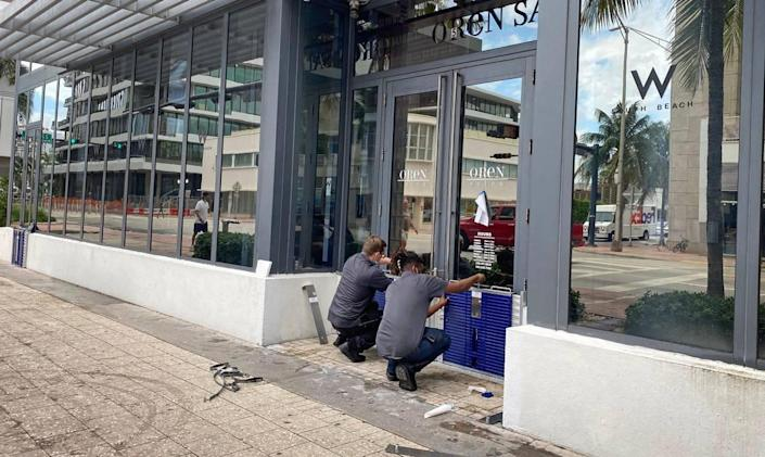 Cody Lazarz and Denton Wright, workers at the W Hotel on South Beach, install flood protection barriers on the doors of the Oren Salon, on the ground floor of the property along Collins Avenue, on Friday morning, August 13, 2021, in preparation for Tropical Depression Fred, which could strengthen to a Tropical Storm as it nears South Florida.