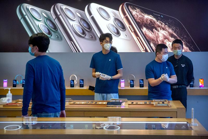 Employees at an Apple store in Beijing wearing masks to prevent the spread of the deadly coronavirus: AP