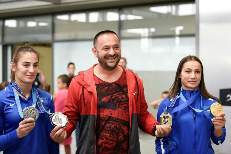 "Kosovo judokas Majlinda Kelmendi (R) and Nora Gjakova (L) show off their European Games medals as they pose with coach Driton ""Toni"" Kuka"