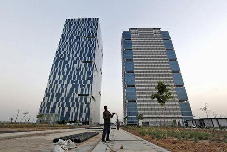 FILE PHOTO: A worker folds cable of welding machine in front of two office buildings at Gujarat International Finance Tec-City at Gandhinagar, in Gujarat