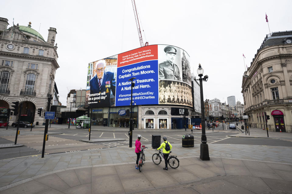 Cyclists look at a billboard honouring Captain Tom Moore the army veteran who has raised millions for the NHS, in Piccadilly Circus, London, Saturday, April 18, 2020. A 99-year-old British veteran who started walking laps in his garden as a humble fundraising campaign for the National Health Service has generated millions of pounds and become a national rallying point during the coronavirus pandemic. (Aaron Chown/PA via AP)