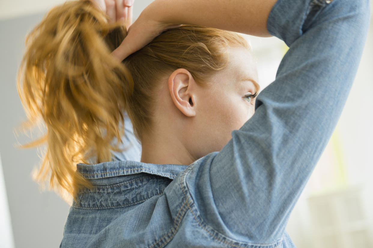 USA, New Jersey, Young woman tying hair