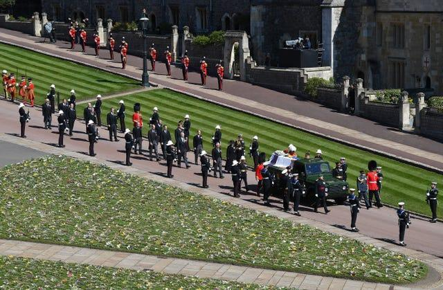 The Duke of Edinburgh's coffin, covered with his Personal Standard, is carried on the purpose-built Land Rover Defender followed by the Princess Royal, the Prince of Wales, the Duke of York, the Earl of Wessex, the Duke of Cambridge, Peter Phillips, the Duke of Sussex, the Earl of Snowdon, Vice Admiral Sir Timothy Laurence outside St George's Chapel, Windsor Castle