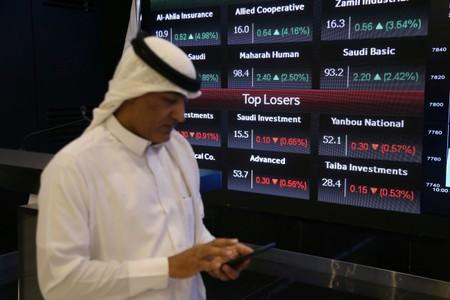 Man walks next to a screen with Saudi Stock Exchange (Tadawul) prices in Riyadh