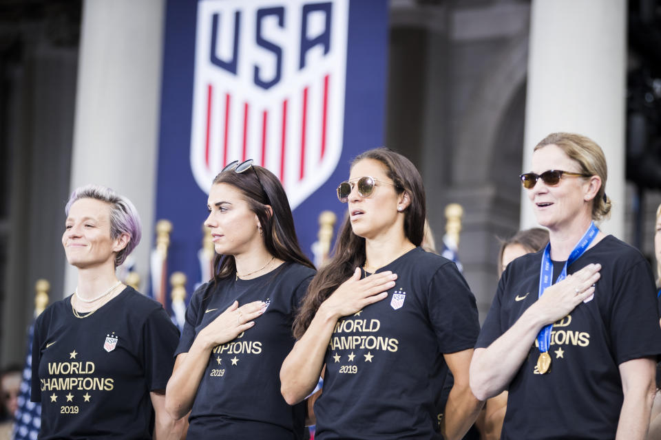 MANHATTAN, NY - JULY 10: Megan Rapinoe #15 of United States stands for the National Anthem but does not hold her hand to her heart.  Alex Morgan #13 of United States, Carli Lloyd #10 of Unites States and Head Coach Jill Ellis hold their hand to their hearts as the USA Women's National Soccer Team stand in front of the 2019 FIFA World Cup Trophy and dance after the City Hall Ceremony.  Each member of the team got a key to the city after winning the 2019 FIFA World Cup Championship title, their fourth, played in France against Netherlands, at the City Hall Ceremony in the Manhattan borough of New York on July 10, 2019, USA.  (Photo by Ira L. Black/Corbis via Getty Images)
