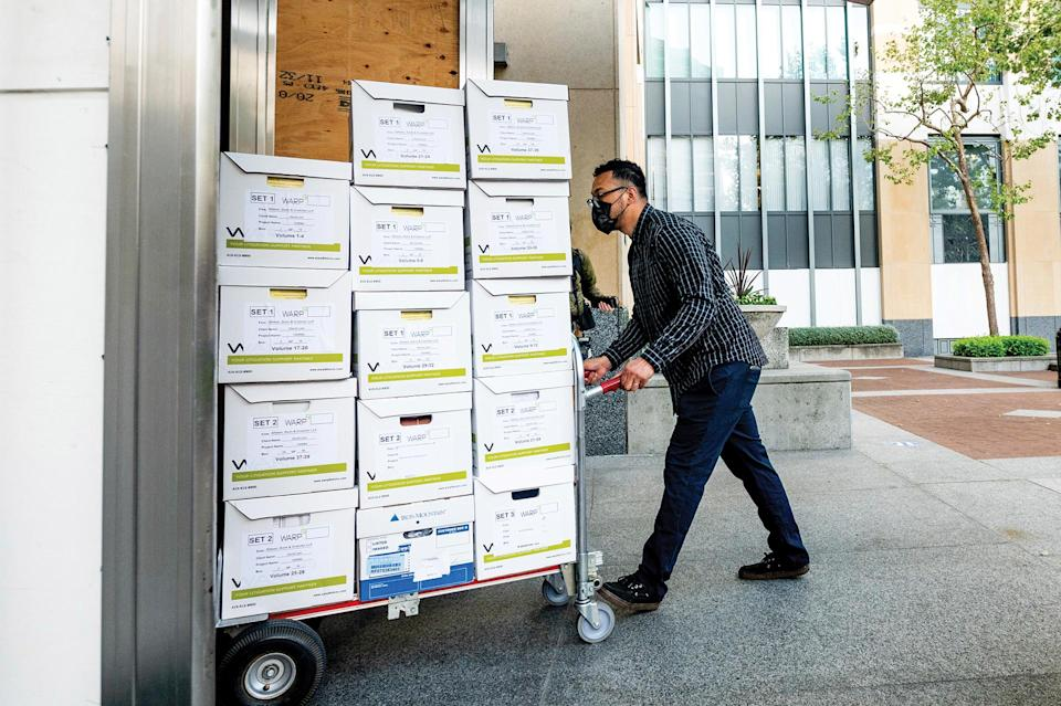 A member of Apple's legal team brings exhibit boxes into the Ronald V. Dellums building in Oakland, Calif., on May 3, as the company battles Epic Games in federal court. - Credit: AP
