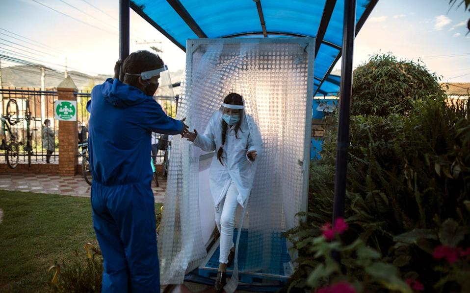 A student wearing protective gear exits a disinfection area on the first day back to in-person class since Spring last year at Liceo Lunita, a private school in Chia on the outskirts of Bogota - AP Photo/Ivan Valencia)