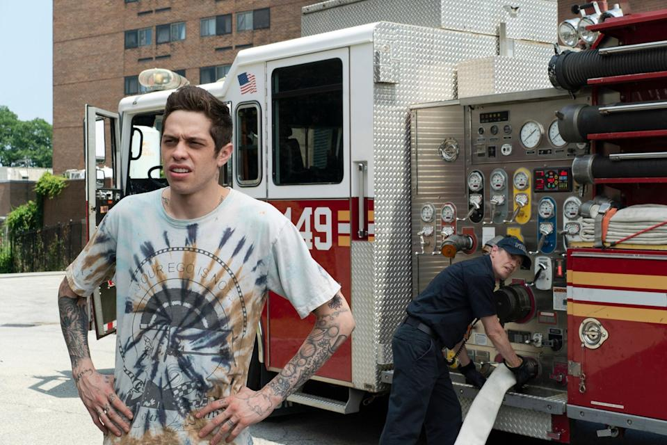 """Pete Davidson poses in front of a firetruck (being worked on by Steve Buscemi) on set of """"The King of Staten Island"""""""
