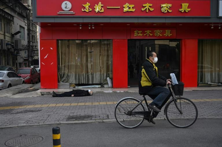 The lifeless body of a man lying on the street, not far from Wuhan hospital