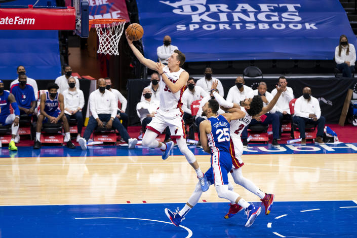 Miami Heat's Duncan Robinson, left, shoots as Miami Heat's Gabe Vincent, right, tries to hold off Philadelphia 76ers' Ben Simmons, center, during the second half of an NBA basketball game, Tuesday, Jan. 12, 2021, in Philadelphia. (AP Photo/Chris Szagola)