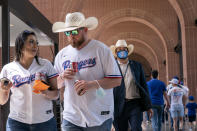 Josh Johnson and Zoe Aguilar walk through the concourse of Globe Life Field before the Texas Rangers home opener baseball game against the Toronto Blue Jays Monday, April 5, 2021, in Arlington, Texas. The Texas Rangers are set to have the closest thing to a full stadium in pro sports since the coronavirus shut down more than a year ago. (AP Photo/Jeffrey McWhorter)