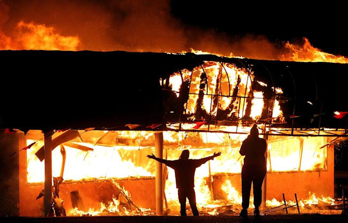 """FILE - In this Nov. 25, 2014 file photo, protesters take their pictures in front of a burning building set afire by protesters in Ferguson, Mo., after the police shooting of Michael Brown. St. Louis wants to spend nearly $10 million to hire and train 160 police officers in response to a recent violent crime hike its mayor and police chief blame on a """"Ferguson effect."""" (AP Photo/St. Louis Post-Dispatch, Robert Cohen, File)"""