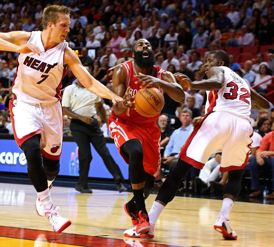 James Harden (C) of the Houston Rockets drives past Justin Hamilton (L) and James Ennis of the Miami Heat during their NBA game at American Airlines Arena in Miami, Florida, on November 4, 2014 (AFP Photo/Mike Ehrmann)