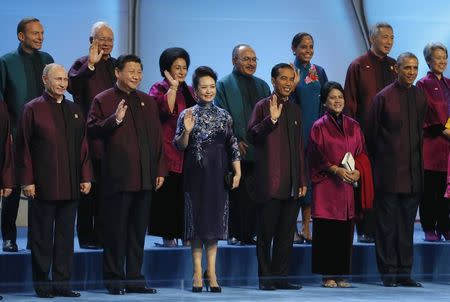 Russian President Vladimir Putin (L) and U.S. President Barack Obama (R) stand with Chinese President Xi Jinping (2nd L) and other leaders during the APEC Summit family photo in Beijing November 10, 2014. Front row: (from L-R) Putin, Xi and his wife Peng Liyuan, Indonesian President Joko Widodo and his wife Iriana, and Obama. Back row: (from L-R) Australia's Prime Minister Tony Abbott, Malaysia's Prime Minister Najib Razak and his wife Rosmah Mansor, Papua New Guinea's Prime Minister Peter O'Neill and his wife Lynda, Singapore's Prime Minister Lee Hsien Loong and his wife Ho Ching. REUTERS/Kevin Lamarque (CHINA - Tags: POLITICS)