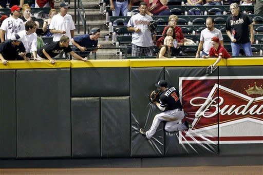 Miami Marlins' Bryan Peterson hits the wall after catching a long fly out by Arizona Diamondbacks' Jake Elmore during the fourth inning of a baseball game, Tuesday, Aug. 21, 2012, in Phoenix. (AP Photo/Matt York)