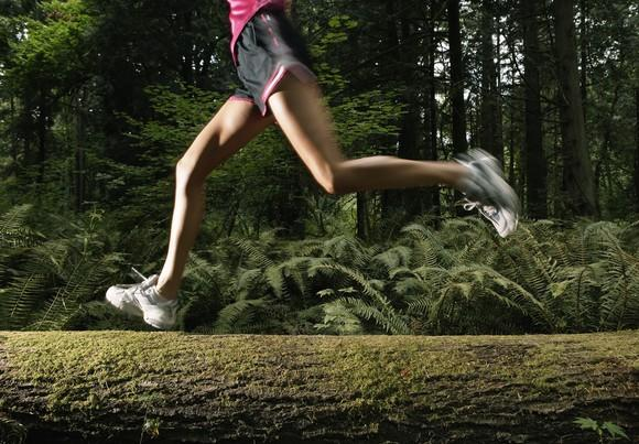 A woman jogs through the woods.