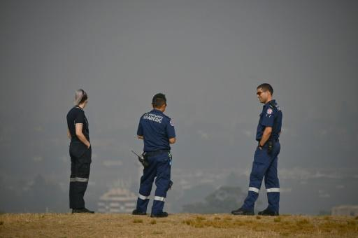 Paramedics take a break as they look out over a smokey haze which blankets Sydney