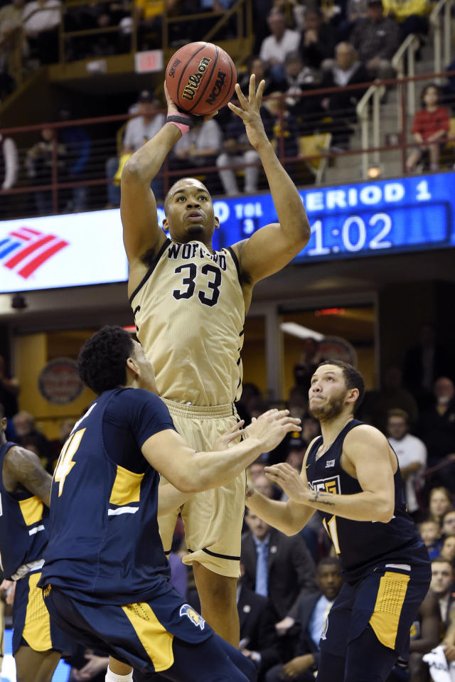 Wofford forward Cameron Jackson (33) shoots over UNC-Greensboro forward Kyrin Galloway (14) and guard Demetrius Troy (11) in the first half of an NCAA college basketball game for the Southern Conference tournament championship, Monday, March 11, 2019, in Asheville, N.C. (AP Photo/Kathy Kmonicek)