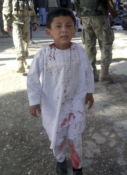 An Afghan boy, who lost his father in a suicide attack, walks around a hospital in a daze in Maymana, Faryab province north west of Kabul, Afghanistan, Friday, Oct. 26, 2012. A suicide bomber blew himself up outside a mosque in northern Afghanistan on Friday, killing dozens of people and wounding scores, government and hospital officials said. (AP Photo/Qawtbuddin Khan)