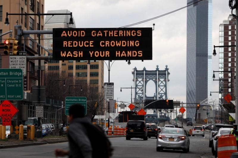 Signage regarding the coronavirus disease (COVID-19) is displayed at the entrance to the Manhattan Bridge in the Brooklyn borough of New York City