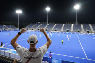 A member of the New Zealand delegation cheers for his team from stands empty of fans due to COVID-19 restrictions during a men's field hockey match against Spain at the 2020 Summer Olympics, Sunday, July 25, 2021, in Tokyo, Japan. (AP Photo/John Minchillo)