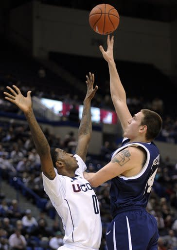 CORRECTS DATELINE TO HARTFORD - New Hampshire's Chris Pelcher, left, shoots over Connecticut's Phillip Nolan during the first half of an NCAA college basketball game in Hartford, Conn., Thursday, Nov. 29, 2012. (AP Photo/Fred Beckham)