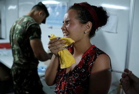 A Venezuelan woman receives a free vaccination given by a volunteer after showing her passport at the Pacaraima border control, Roraima state, Brazil August 9, 2018. REUTERS/Nacho Doce
