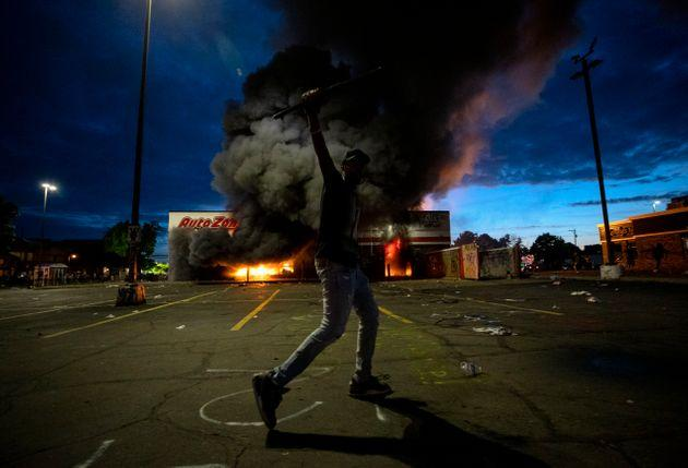 A man poses for a photo in the parking lot of an AutoZone store in flames, while protesters hold a rally for George Floyd in Minneapolis on Wednesday.