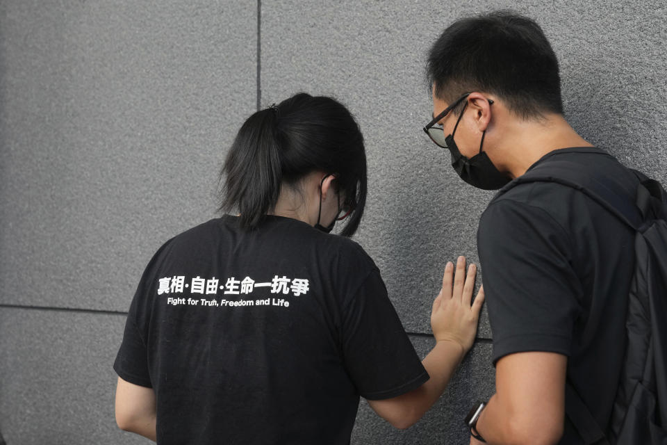 Chow Han Tung, vice chairwoman of the Hong Kong Alliance in Support of Patriotic Democratic Movements of China, left, speaks to a committee member before delivering a letter to the police to reject their information request at the police headquarters in Hong Kong, Tuesday, Sept. 7, 2021. The group said the Hong Kong government is arbitrarily labeling pro-democracy organizations as foreign agents so they can be prosecuted under a tough national security law, Tuesday. (AP Photo/Kin Cheung)