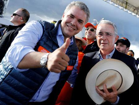 FILE PHOTO: Colombian former president Alvaro Uribe (R) and right-wing presidential candidate Ivan Duque pose during a closing campaign rally in Bogota, Colombia May 20, 2018. REUTERS/Nacho Doce/File Photo