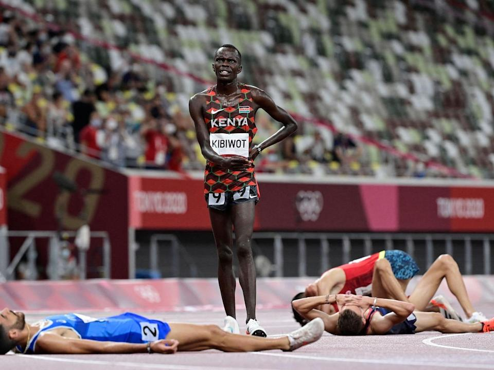 Kenya's Abraham Kibiwot stands after the steeplechase while runners lay on the ground.