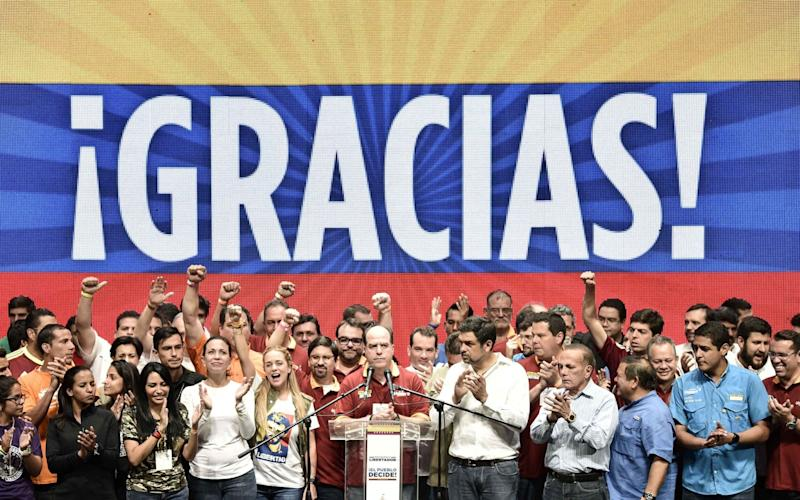 Julio Borges, president of Venezuela's National Assembly, center, gives a speech as opposition leaders celebrate the result of a symbolic Venezuelan plebiscite. - Bloomberg