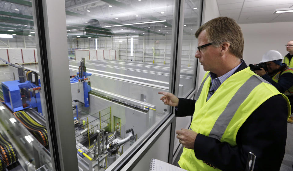 "FILE - In this May 19, 2016, file photo, Eric Lindblad, vice president in charge of the Boeing 777X wing, looks over the ""clean"" room area of the new 777X Composite Wing Center, a day ahead of its grand opening in Everett, Wash. Lindblad, the executive who manages the Boeing 737 Max program and the Seattle-area factory where the now-grounded plane is built, said he planned to retire last summer, and a Boeing spokesman said Thursday, July 11, 2019, that Lindblad's decision was unrelated to two deadly accidents involving Max jets. (AP Photo/Elaine Thompson, File)"