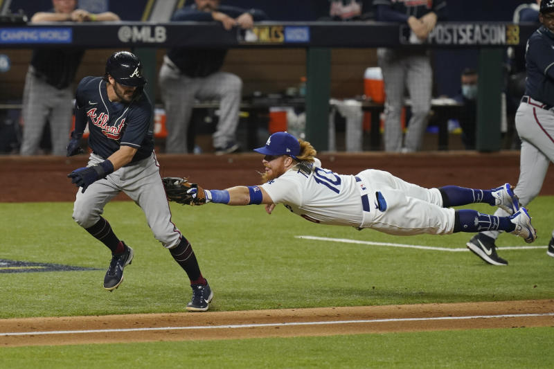 Los Angeles Dodgers third baseman Justin Turner tags Atlanta Braves' Dansby Swanson in a run down during the fourth inning in Game 7 of a baseball National League Championship Series Sunday, Oct. 18, 2020, in Arlington, Texas. (AP Photo/Eric Gay)