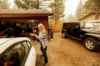 As the Caldor Fire approaches, Patty Kingsbury carries a teddy bear while evacuating from her South Lake Tahoe, Calif., home on Friday, Aug. 27, 2021. (AP Photo/Noah Berger)