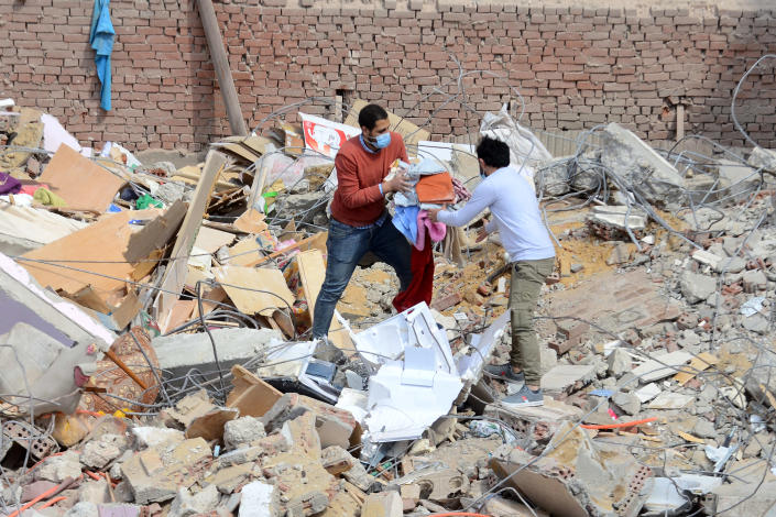 People carry their belongings on the rubble of a collapsed apartment building in the el-Salam neighborhood, in Cairo, Egypt, Saturday, March 27, 2021. A nine-story apartment building collapsed in the Egyptian capital early Saturday, killing at several and injuring about two dozen others, an official said. (AP Photo/Tarek wajeh)