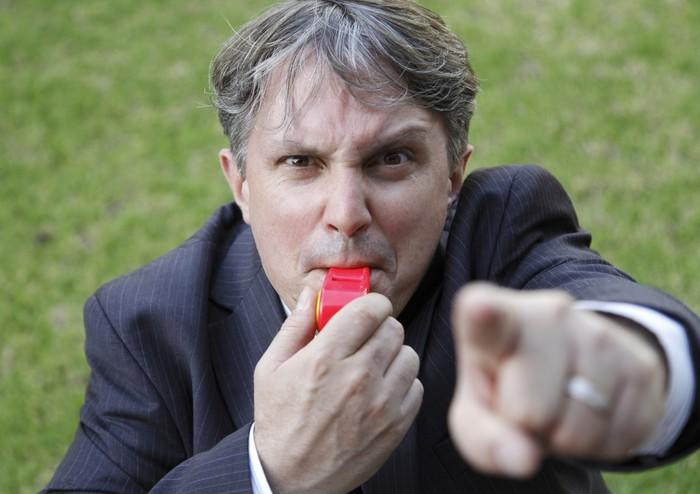 A man in a suit with an angry look pointing his finger and blowing a whistle.