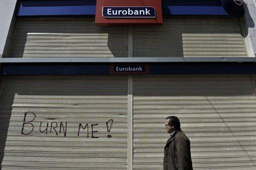 A man walks past a closed bank during a strike in Athens in 2011