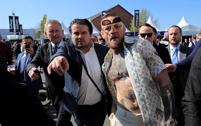 Conor McGregor, centre-right, arrives at Aintree Racecourse on Saturday afternoon - PA