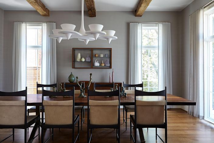 """In the formal dining room, Liss paired a walnut-slab table from <a href=""""http://www.bddw.com"""" rel=""""nofollow noopener"""" target=""""_blank"""" data-ylk=""""slk:BDDW"""" class=""""link rapid-noclick-resp"""">BDDW</a> with eight <a href=""""https://www.espasso.com/products/2165/cantu-high-dining-chair-by-sergio-rodrigues#5"""" rel=""""nofollow noopener"""" target=""""_blank"""" data-ylk=""""slk:Sergio Rodrigues"""" class=""""link rapid-noclick-resp"""">Sergio Rodrigues</a> Cantu chairs, and found a vintage Franco Albini cabinet (at New York's <a href=""""https://www.donzella.com/contact"""" rel=""""nofollow noopener"""" target=""""_blank"""" data-ylk=""""slk:Donzella"""" class=""""link rapid-noclick-resp"""">Donzella</a>) to complete the space. A wall vitrine, also by Albini, shows a collection of vessels by the Haas Brothers. The Nuage chandelier, a distinctive design in sculpted plaster, was custom made by Alexandre Logé."""