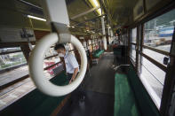 Yuta Azumi, of the train planning division of Hiroshima Electric Railway Co., Ltd., walks inside a tram which survived the Hiroshima atomic bombing at a train maintenance facility in Hiroshima, western Japan, Monday, Aug. 3, 2020. It has been restored and repainted its original colors, will run on the street on Aug. 6 to commemorate the day of the U.S. first atomic bombing in the city. (AP Photo/Eugene Hoshiko)