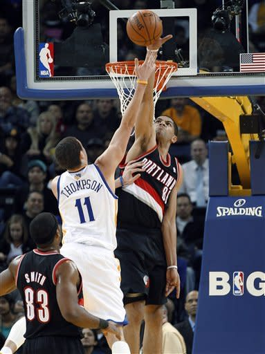 Portland Trail Blazers' Nicolas Batum (88) blocks a shot by Golden State Warriors' Klay Thompson (11) as Trail Blazers' Craig Smith (83) watches during the first half of an NBA basketball game in Oakland, Calif., Wednesday, Feb. 15, 2012. (AP Photo/Tony Avelar)