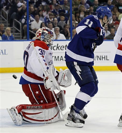 Tampa Bay Lightning's Tom Pyatt, right, deflects a puck past Washington Capitals goalie Michal Neuvirth, of the Czech Republic, during the second period of an NHL hockey game Monday, April 2, 2012, in Tampa, Fla. (AP Photo/Mike Carlson)